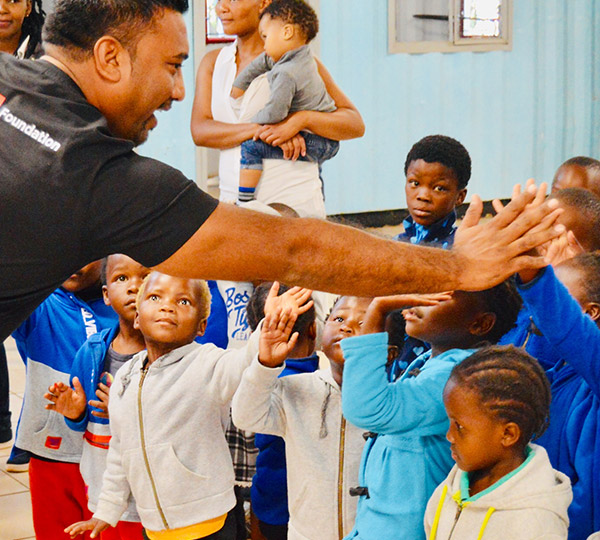 Lenovo Foundation leader giving high five to children