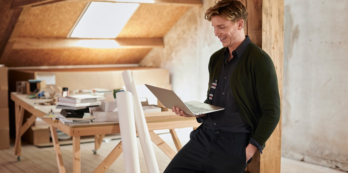 Shot of a young man in an a architect's studio holding his Lenovo IdeaPad S540