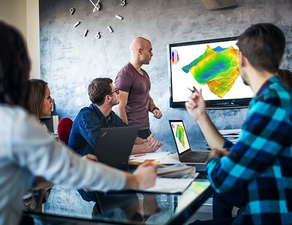 Group of people in a conference room with Lenovo ThinkPad P15 Gen 2 mobile workstations and a wall display mirroring one of the laptops.