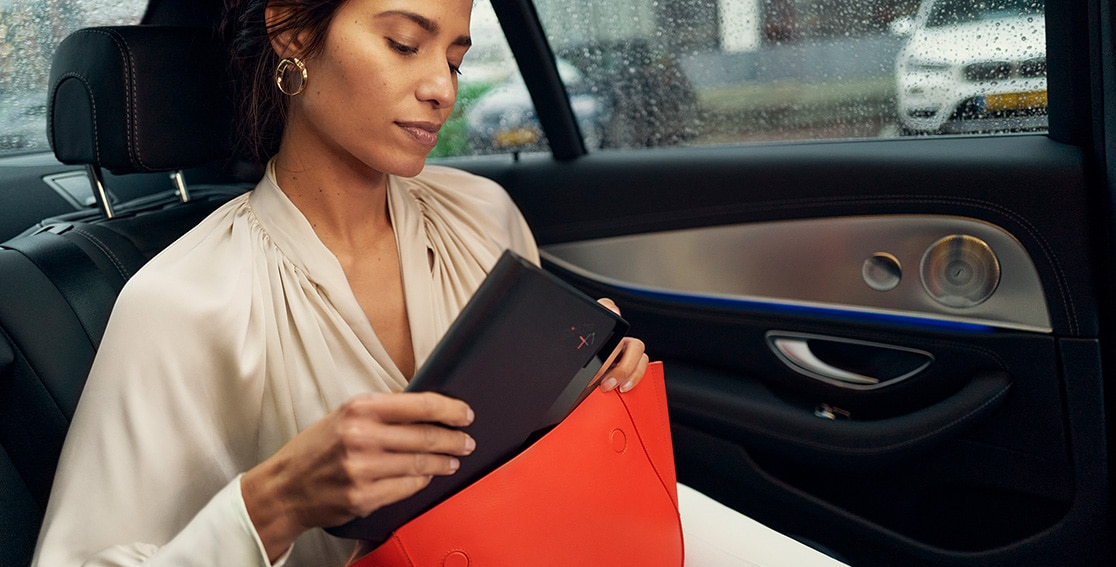 Woman sitting in a car pulling a folded Lenovo ThinkPad X1 Fold out of her red handbag