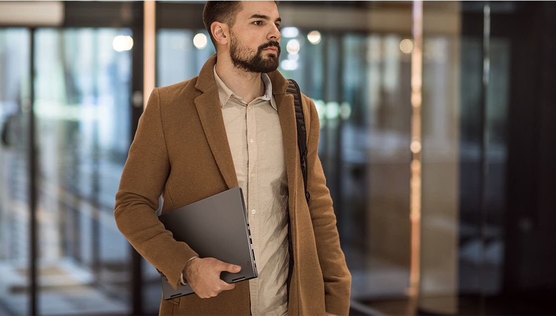 Hipster guy carrying a Lenovo ThinkPad X1 Yoga Gen 4  2-in-1 laptop under his arm.