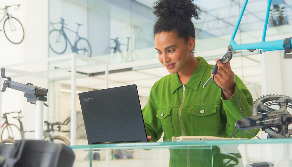 Woman fixing a bicycle in clean modern bike shop, viewing content on her Lenovo Yoga laptop.