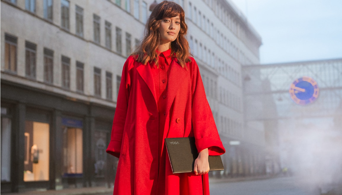 Woman in fashionably dramatic red outfit holding a Lenovo Yoga Slim laptop with black leather finish, standing in middle of moody city streetscape.