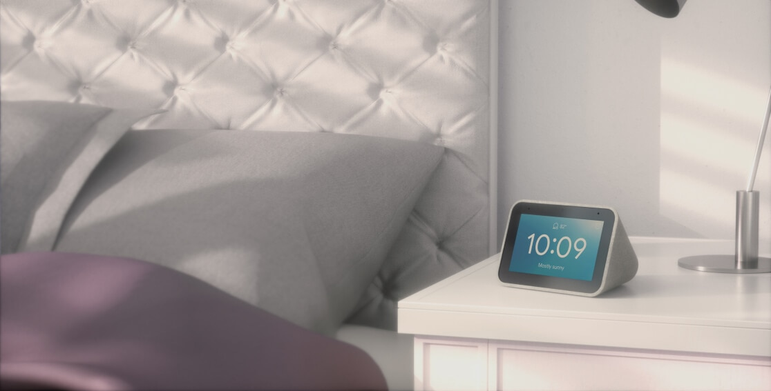Lenovo Smart Clock with the Google Assistant on a bedside table, showing the time and weather.