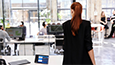 Thumbnail of woman with red hair and black blazer walking away from desk where ThinkSmart View Zoom is sitting.