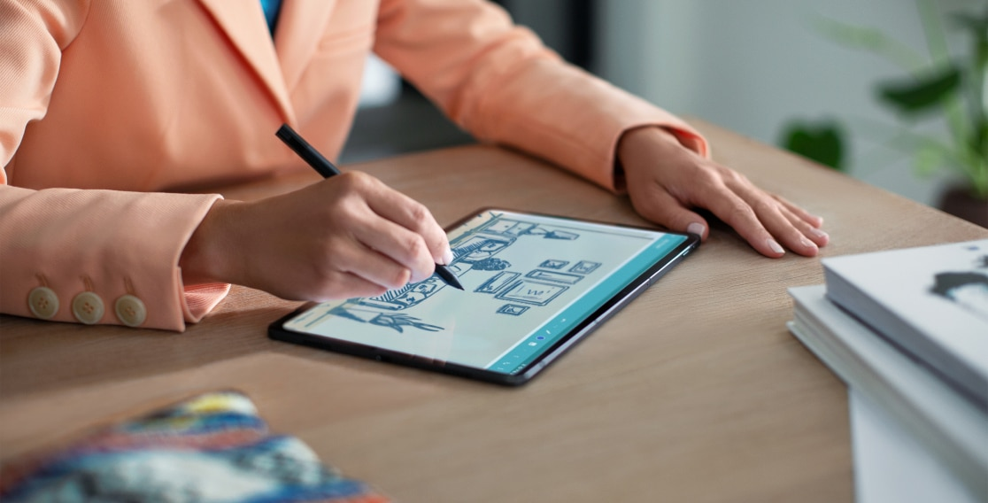 Lenovo Tab P11 Pro lying flat on a table with man using optional Lenovo Precision Pen to draw on tablet