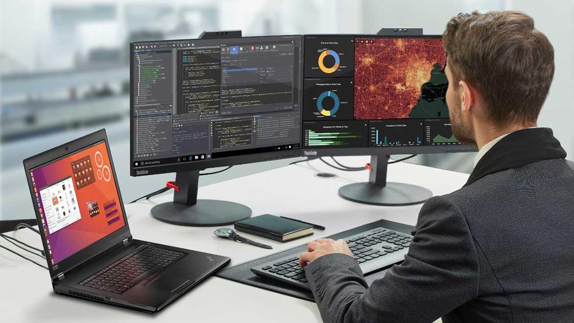 Man programming and analyzing data using ThinkPad laptop connected to mulitple ThinkVision monitors